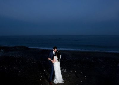 Candlelit heart with bride and groom on the beach