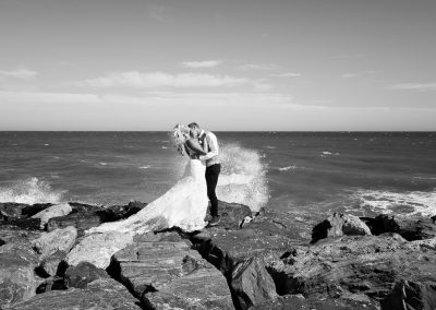 Sea splashing bride and groom in Benalmadena
