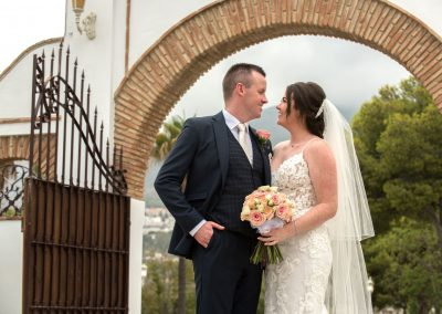 Bride and groom at finca arch